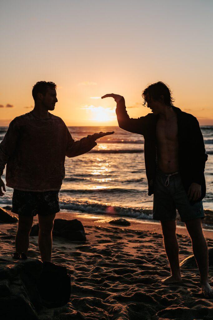 mezczyzni zbijaja sobie piatke na plazy